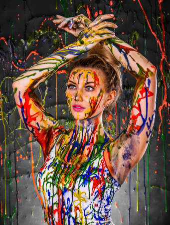 paints: Beautiful young woman covered with multicolored paints Stock Photo