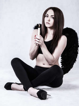 dark angel: Beautiful young woman in a costume of the fallen angel holding a candle over grey background