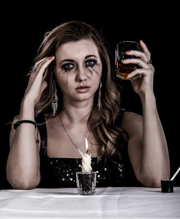 heavy heart: Depressed young woman with a glass of whiskey over black background