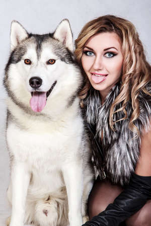 Beautiful young woman with a husky dog over grey background Stock Photo