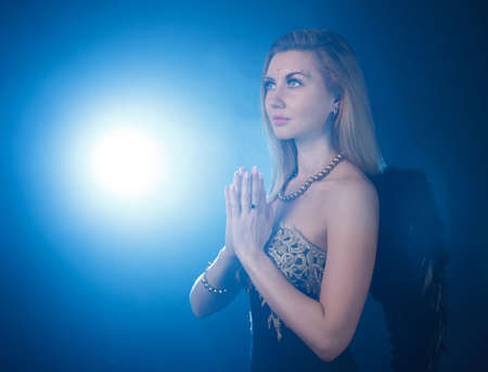 godlike: Portrait of woman with dark angel wings praying at the background of the blue light