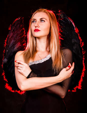 succubus: Beautiful young woman with black angel wings over black background Stock Photo