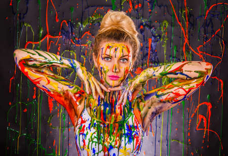 splashed: Beautiful young woman covered with multicolored paints Stock Photo
