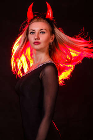 Beautiful young woman with red demon horns and red hair over black background