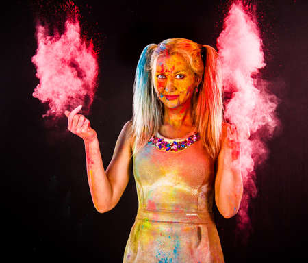 Beautiful young woman covered with colored powder over dark background