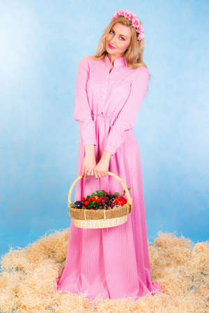 staying: Beautiful young blonde in a long pink dress staying in a hay over cyan background