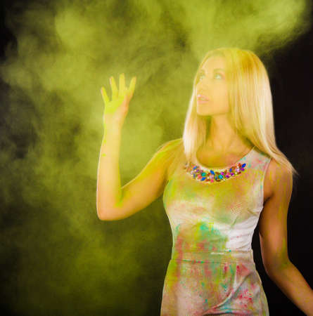 colored powder: Beautiful young woman covered with colored powder over dark background
