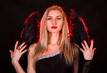 succubus: Beautiful young woman with black angel wings over dark red background