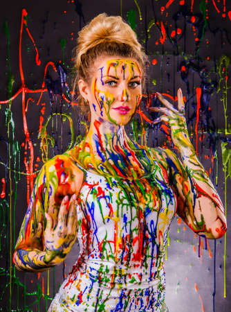 color model: Beautiful young woman covered with multicolored paints Stock Photo