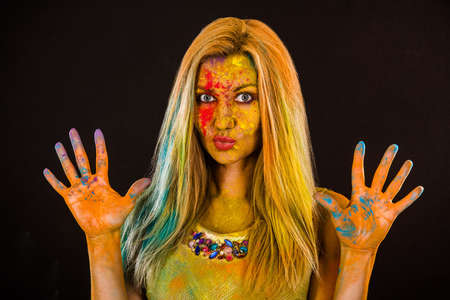 colored powder: Beautiful young woman with colored powder over dark backgrond Stock Photo
