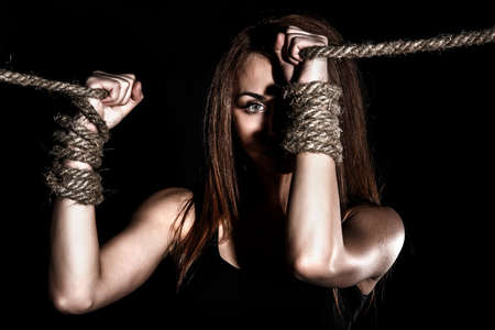 hobble: Beautiful young woman with tied arms over black background