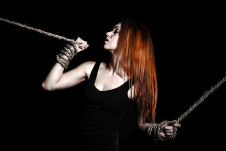 tied woman: Beautiful young woman with bright red hair and tied arms over black background Stock Photo