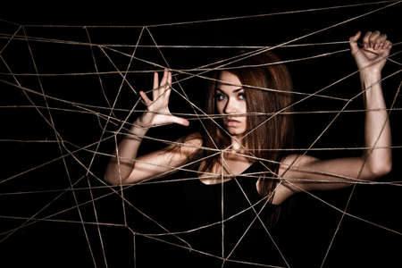 hobble: Beautiful young woman behind the net of ropes over black background Stock Photo