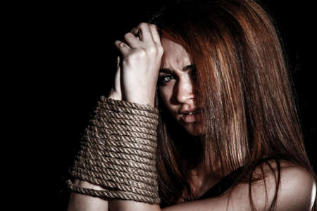 incarceration: Beautiful young woman with tied arms over black background