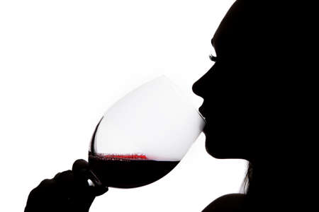 Silhouette of a woman drinking the wine