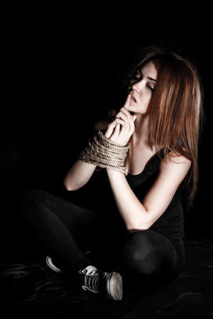 Beautiful young woman with tied arms sitting on the floor over black background