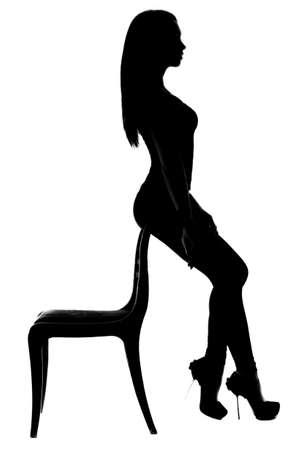 mujer desnuda sentada: Silueta de una mujer sentada en la parte posterior de la silla Foto de archivo
