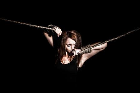 gefesselt: Schöne junge Frau mit gebundenen Armen auf schwarzem Hintergrund