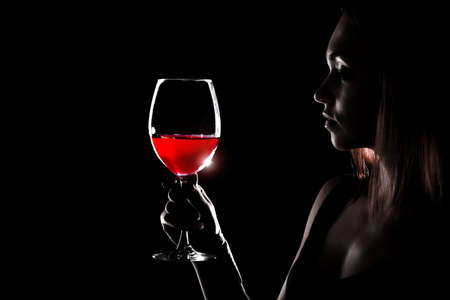 Beautiful young woman holding the glass of a red wine in darkness