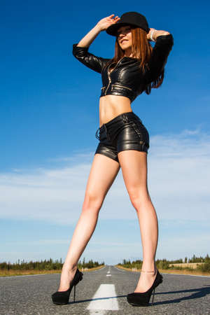 Sexy woman in a black leather clothes staying on the road