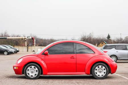 escarabajo: UFA, RUSIA - 19 de abril de 2012: coche compacto rojo Volkswagen Beetle en el centro de comercio de coches usados.