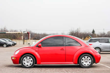 from side: UFA, RUSSIA - APRIL 19, 2012: Red compact car Volkswagen Beetle in the used cars trade center.