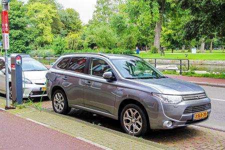outlander: AMSTERDAM, NETHERLANDS - AUGUST 10, 2014: Motor car Mitsubishi Outlander P-HEV charging at the city street.