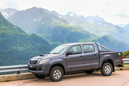 GOTTHARD PASS, SWITZERLAND - AUGUST 5, 2014: Motor car Toyota Hilux at the high Alpine mountain road. Editorial