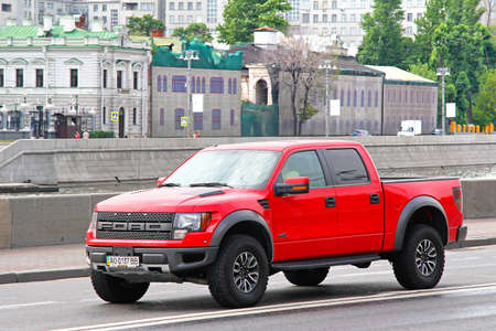 MOSCOW, RUSSIA - JULY 7, 2012: Red pickup truck Ford F-150 Raptor at the city street. Редакционное