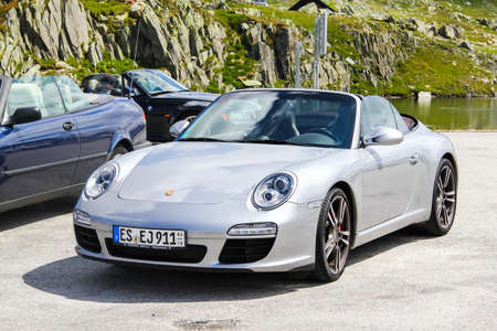 supercar: GOTTHARD PASS, SWITZERLAND - AUGUST 5, 2014: Silver supercar Porsche 991 911 at the high mountain Alpine road. Editorial
