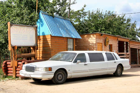 limo: YAROSLAVL REGION, RUSSIA - AUGUST 26, 2011: White limousine Lincoln Town Car parked near the wooden buildings. Editorial