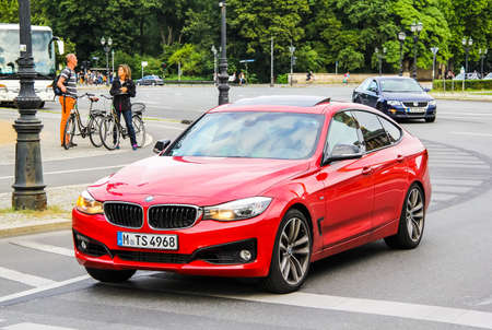 capacious: BERLIN, GERMANY - AUGUST 15, 2014: Modern red car BMW F34 3-series GT at the city street.