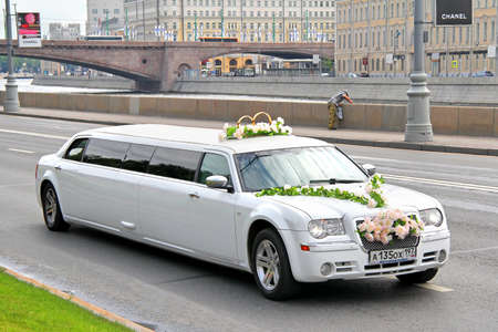 limousine: MOSCOW, RUSSIA - JULY 7, 2012: White limousine Chrysler 300C at the city street.