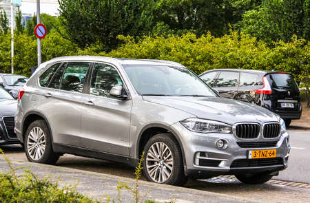 crossover: ROTTERDAM, NETHERLANDS - AUGUST 9, 2014: Modern crossover BMW F15 X5 at the city street.