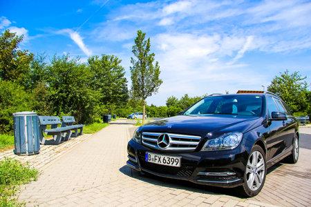 BRANDENBURG, GERMANY - JULY 20, 2014: Motor car Mercedes-Benz W204 C180 at the parking near the interurban freeway.