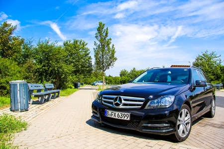 BRANDENBURG, GERMANY - JULY 20, 2014: Motor car Mercedes-Benz W204 C180 at the parking near the interurban freeway.