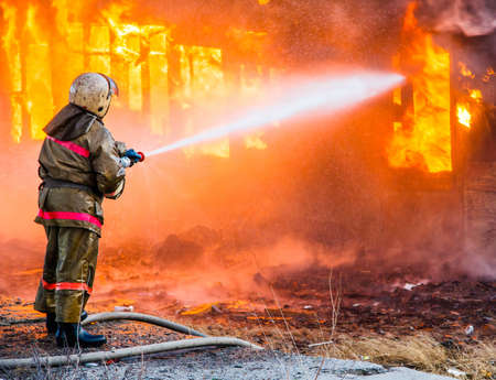 bombero de rojo: Fireman extinguishes a burning old wooden residential house.