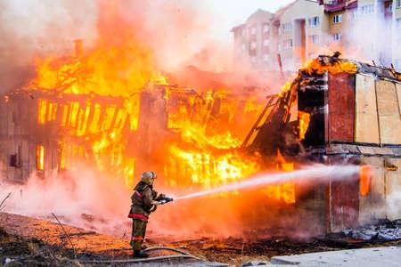 bombero de rojo: Bombero extingue un incendio en una vieja casa de madera Foto de archivo