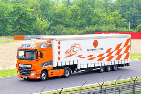 formula one: BUDAPEST, HUNGARY - JULY 27, 2014: Orange semi-trailer truck DAF XF at the Hungaroring Formula One Race Track. Editorial