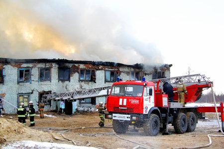 burning house: NOVYY URENGOY, RUSSIA - MAY 9, 2015: Modern fire ladder KAMAZ 43114 AL-30 near the burning old wooden residential house.