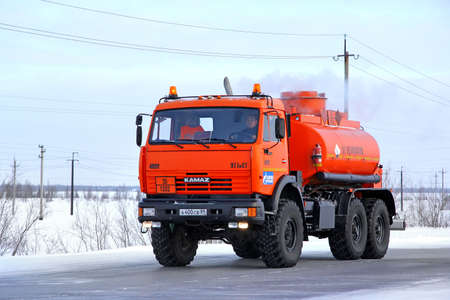 cistern: NOVYY URENGOY, RUSSIA - FEBRUARY 14, 2015: Orange off-road cistern truck KAMAZ 43114 at the interurban road.