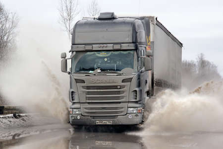 ASHA, RUSSIA - MARCH 15, 2015: Black semi-trailer truck Scania R420 at the city street during a strong flood. Редакционное