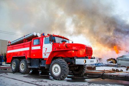 bombero de rojo: Novyy Urengoy, Rusia - 14 de mayo, 2015: cami�n de bomberos rojo Ural 5557 participa en la extinci�n de un incendio en una vieja casa de madera.