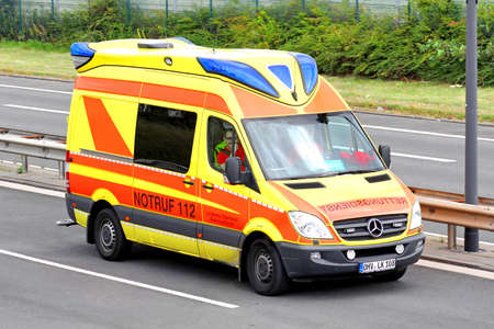 BERLIN, GERMANY - AUGUST 17, 2014: Yellow ambulance car Mercedes-Benz Sprinter at the city street.