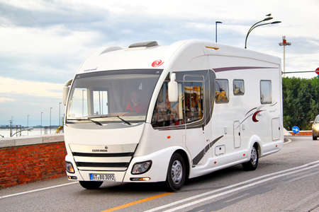 campervan: VENICE, ITALY - JULY 30, 2014: White modern caravan Eura Mobil Integra Style at the city street. Editorial
