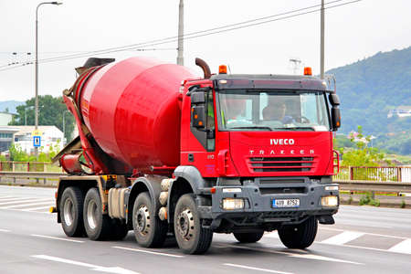 concrete mixer truck: USTI NAD LABEM, CZECH REPUBLIC - JULY 21, 2014: Red concrete mixer truck Iveco Trakker at the city street. Editorial