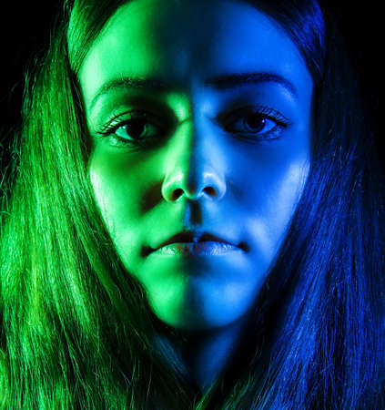 insensitive: Beautiful young woman in green and blue lights over black background Stock Photo