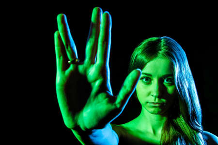 alien face: Beautiful young woman in green light showing the alien sign over black background