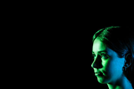 black eye: Beautiful young womans face in blue and green lights at the corner over black background