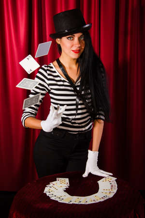 magician: Beautiful young magician with a pack of playing cards